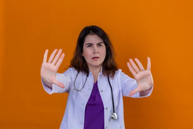 Camice d'uso di medico invecchiato mezzo e con lo stetoscopio con le mani aperte che fanno il fanale di arresto con l'espressione seria e sicura