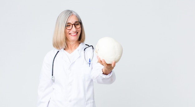 Middle-aged doctor woman holding a skull