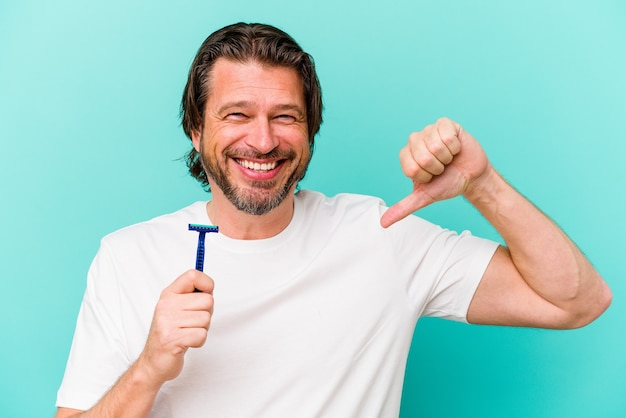 Middle aged dutch man holding a razor blade isolated on blue wall feels proud and self confident, example to follow