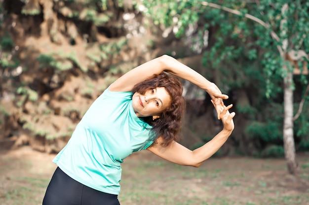 屋外の公園で運動をしている中年高齢者アクティブな女性