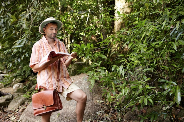 Middle aged european biologist or ecologist wearing hat and briefcase reading notes in his notebook during environmental studies outdoors, conducting research of plants, exploring tropical forest