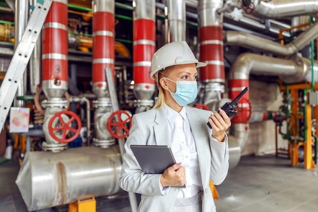 Опытная трудолюбивая женщина-руководитель средних лет в костюме с маской и шлемом держит планшет и разговаривает по рации, стоя на теплоцентрали во время вспышки вируса короны.