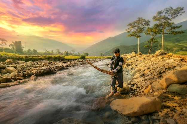 Middle aged farmer playing a musical instrument by the edge of the stream in the countryside in the north of vietnam