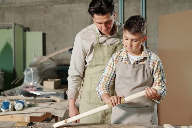 Middle-aged father in apron controlling how his teenage son working with wood in carpentry workshop