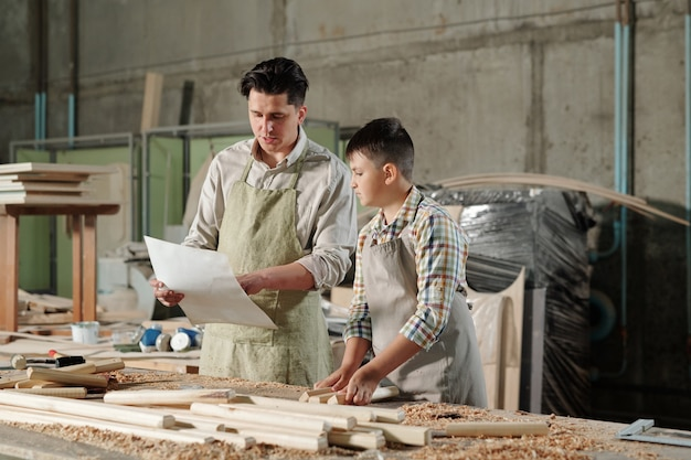 Middle-aged father in apron discussing blueprint with teenage son while they assembling furniture in workshop