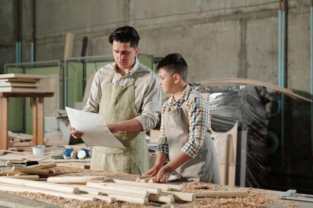 彼らがワークショップで家具を組み立てている間、10代の息子と青写真を話し合うエプロンの中年の父