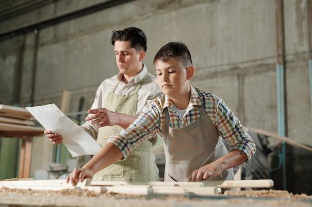 ワークショップで木製家具を組み立てる息子に青写真を読んでエプロンの中年の父