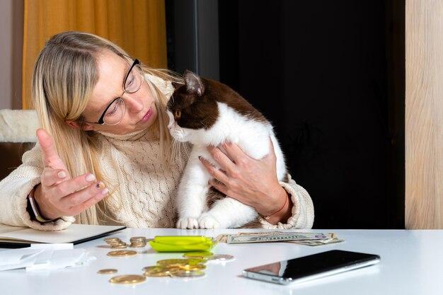 Бухгалтер женщина средних лет, работающая дома и в покое, берет кошку на колени и разговаривает с ней, концепция образа жизни