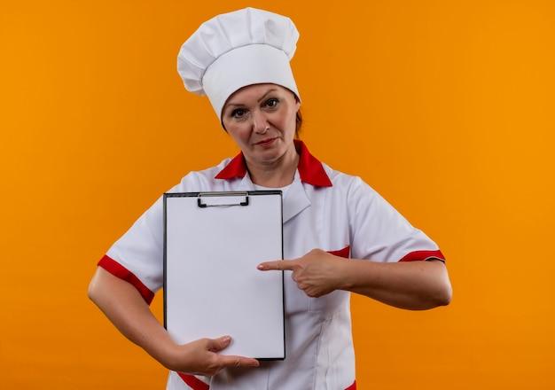 Cuoca di mezza età in uniforme da chef punta il dito negli appunti in mano sul muro giallo isolato