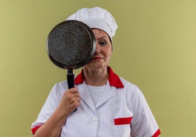 孤立した緑の壁にフライパンで目を覆ったシェフの制服を着た中年女性料理人