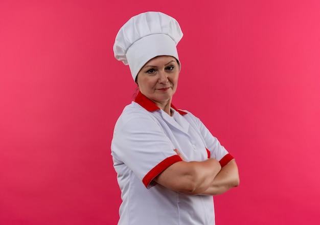 コピースペースと孤立したピンクの壁に手を交差させるシェフの制服を着た中年女性料理人
