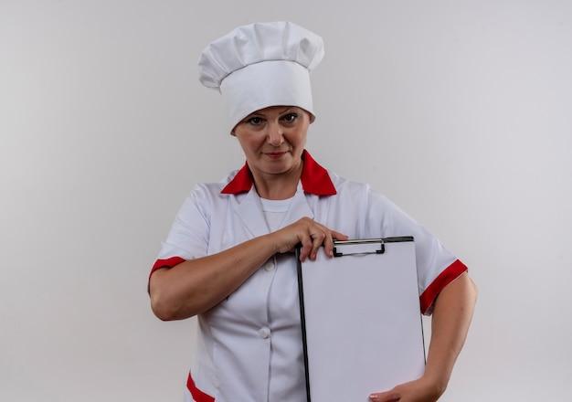 孤立した白い壁にクリップボードを保持しているシェフの制服を着た中年女性料理人