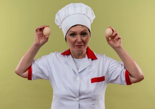 孤立した緑の壁に卵を保持しているシェフの制服を着た中年女性料理人