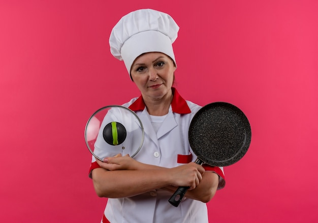 コピースペースと孤立したピンクの壁にフライパンと蓋を保持しているシェフの制服を着た中年女性料理人