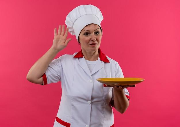 シェフの制服保持プレートの中年女性料理人は、コピースペースと孤立したピンクの壁に挨拶します