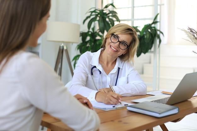 사무실에서 환자와 상담 중인 중년 여성 의사 치료사.