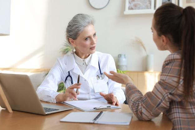 在宅患者と相談中の中年女性医師セラピスト。