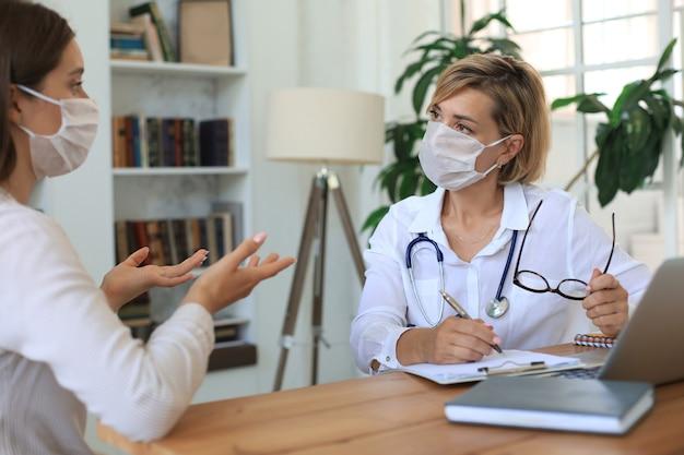 在宅患者と相談の上、医療用マスクの中年女性医師セラピスト。