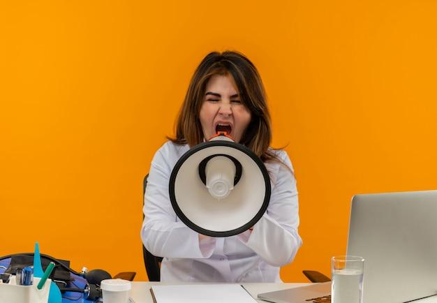 의료 가운과 청진기를 착용하는 중년 여성 의사 의료 도구 클립 보드와 노트북이 고립 된 닫힌 눈을 가진 시끄러운 스피커에서 소리와 함께 책상에 앉아