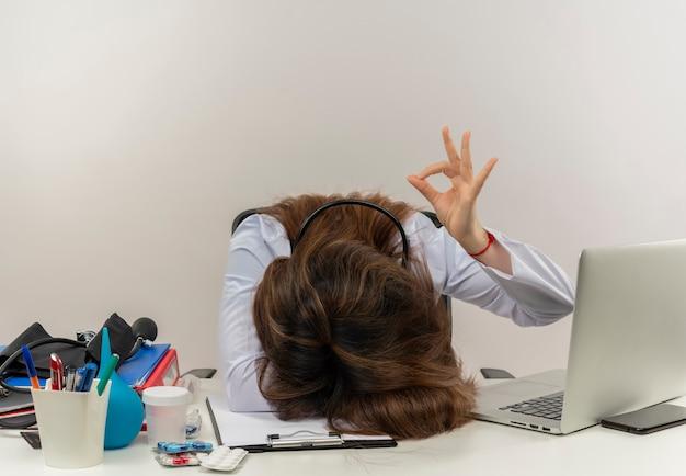 Женщина-врач средних лет, одетая в медицинский халат со стетоскопом, сидит за столом, работает на ноутбуке с медицинскими инструментами, опустила голову и показывает жест окей на белой стене с копией пространства