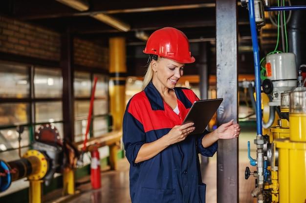 Сотрудница средних лет в рабочем костюме со шлемом на голове с помощью планшета, чтобы проверить давление на машину, стоя на теплоцентрали.