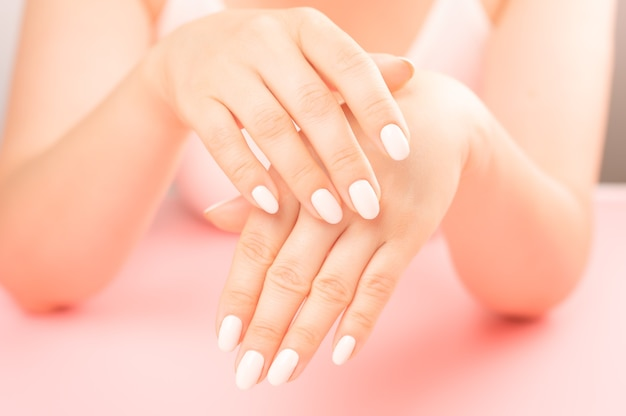 中年女性の手のひら。美しいグラマーマニキュア。手と爪に気を配り、肌をきれいにします。ビューティーサロンでのプロのマニキュア。衛生と手のケア。美容業界のコンセプト。