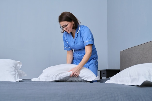 Middle aged female professional maid making bed in hotel room
