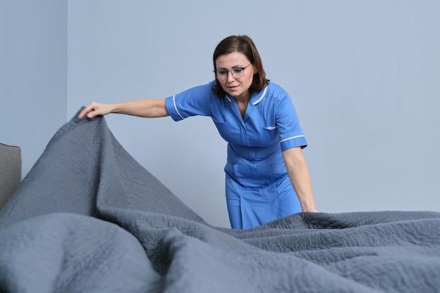 ホテルの部屋でベッドを作る中年女性のプロのメイド。サービス、清掃、スタッフ、ホテルのコンセプト
