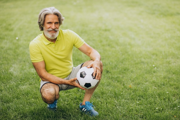 Middle aged football player with football ball