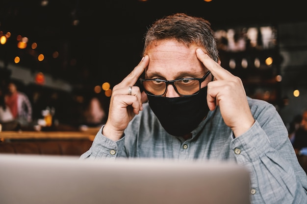 Middle aged freelancer with eyeglasses and facial protective mask on sitting in cafe, having fingers on forehead and thinking how to solve problem. corona outbreak.