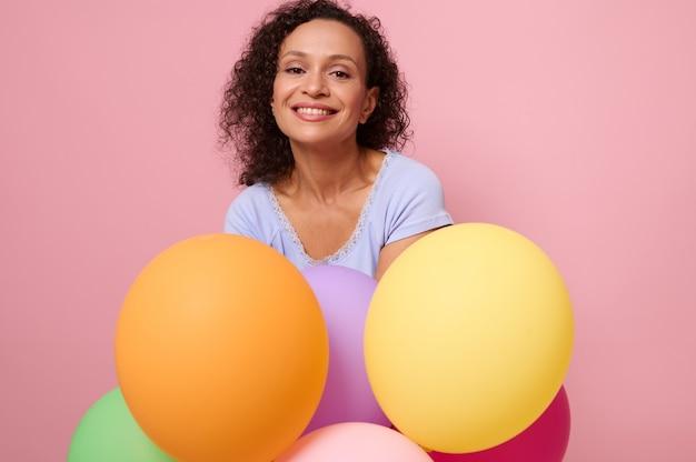中年のフレンドリーで陽気なアフリカ系アメリカ人の女性は、コピースペースでピンクの背景に膨らんだ風船でポーズをとって、カメラを見て歯を見せる笑顔を浮かべます。広告のための美しい女性のスタジオショット