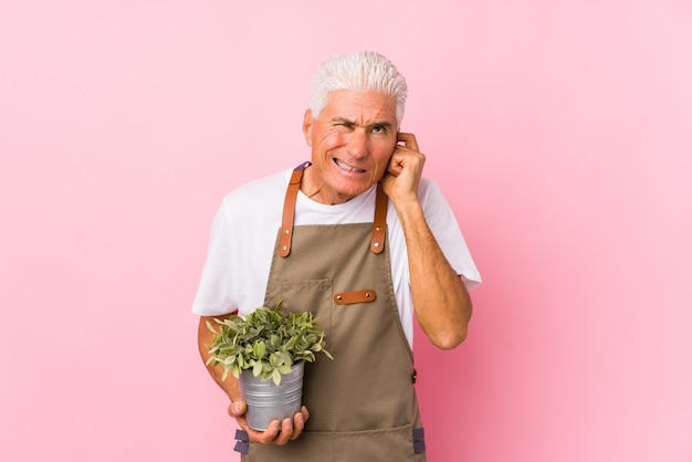 Middle aged gardener man isolated covering ears with hands.