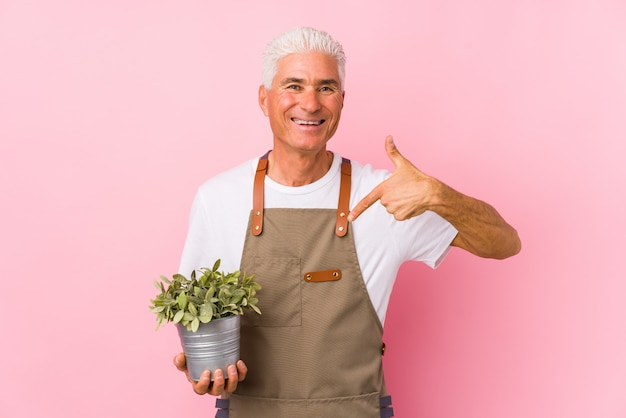 Middle aged gardener man isolated person pointing by hand to a shirt copy space, proud and confident