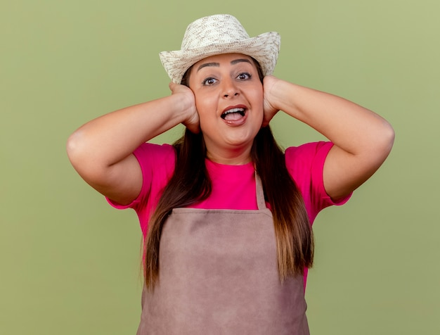 Giardiniere donna di mezza età in grembiule e cappello che copre le orecchie con le mani felici e allegre