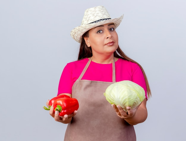 Middle aged gardener woman in apron and hat holding bell pepper and cabbage looking confidenrt