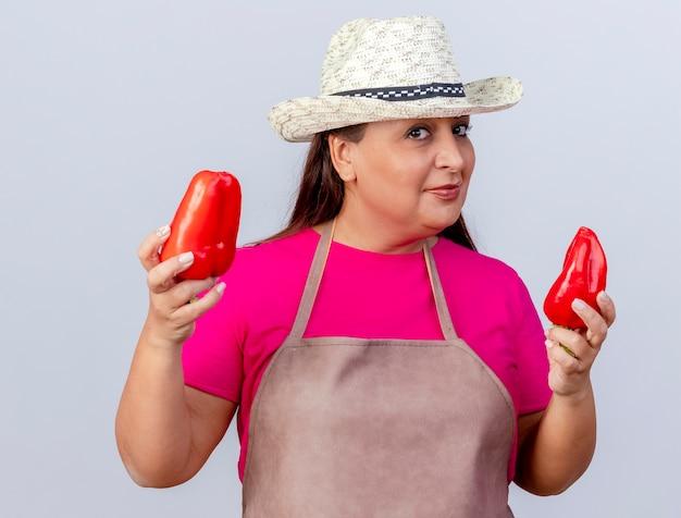 Giardiniere donna di mezza età in grembiule e cappello che tiene peperoni rossi freschi guardando la fotocamera sorridente in piedi fiducioso su sfondo bianco
