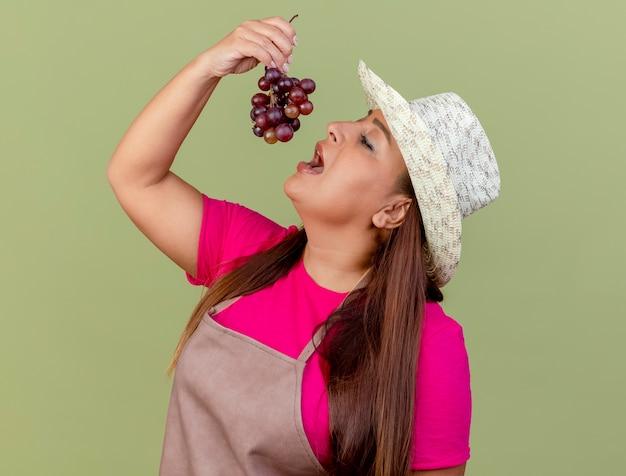 Giardiniere donna di mezza età in grembiule e cappello tenendo l'uva
