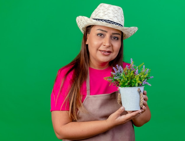 Middle aged gardener woman in apron and hat holding potted plant