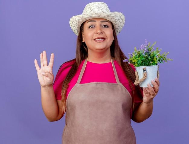 Giardiniere donna di mezza età in grembiule e cappello che tiene pianta in vaso