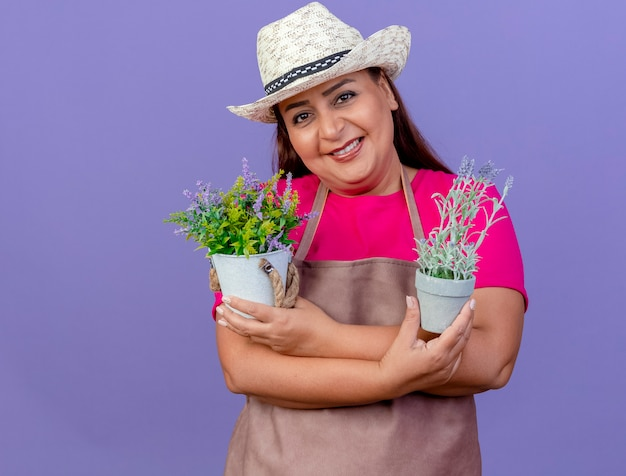 Giardiniere donna di mezza età in grembiule e cappello tenendo le piante in vaso guardando la fotocamera sorridente con la faccia felice in piedi su sfondo viola