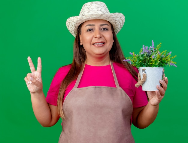 Middle aged gardener woman in apron and hat holding potted