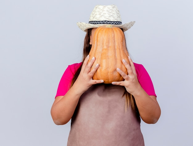 Middle aged gardener woman in apron and hat holding pumpkin hiding her face standing over white background