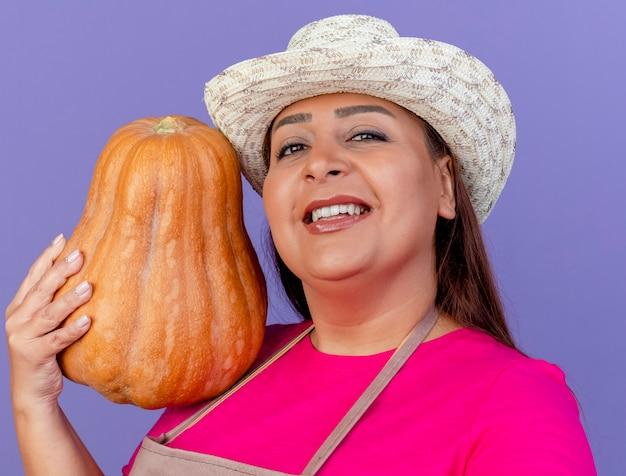Giardiniere donna di mezza età in grembiule e cappello tenendo la zucca con il sorriso sul viso