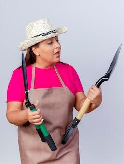 Giardiniere di mezza età donna in grembiule e cappello tenendo la pala e tagliasiepi a guardarli essendo confusi cercando di fare scelta in piedi su sfondo bianco