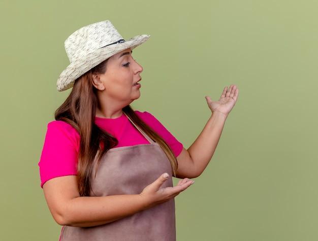 Giardiniere donna di mezza età in grembiule e cappello che presenta qualcosa con le braccia cercando fiducioso in piedi su sfondo chiaro