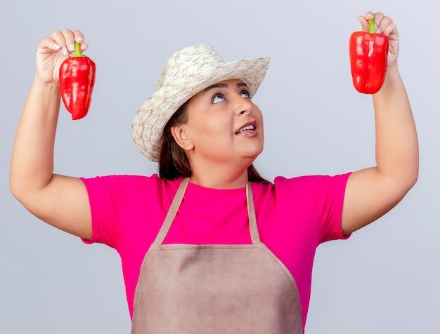 Giardiniere donna di mezza età in grembiule e cappello che mostra peperoni rossi freschi sorridendo guardandoli in piedi su sfondo bianco
