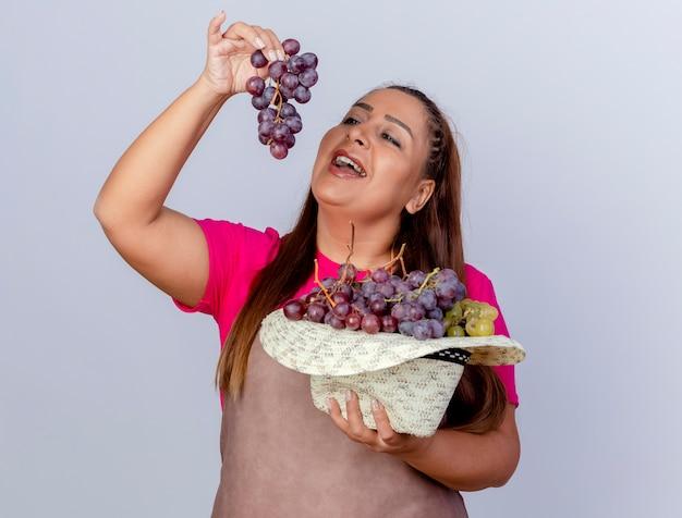 Donna di mezza età giardiniere in grembiule con cappello pieno di uva cercando di assaggiarlo