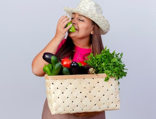 Женщина-садовник средних лет в фартуке и шляпе держит ящик, полный овощей, ощущает приятный аромат свежего болгарского перца
