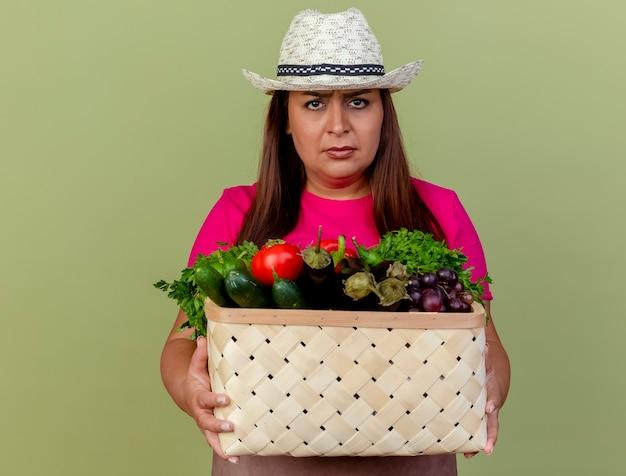 밝은 배경 위에 서 심각한 얼굴로 카메라를보고 야채 가득한 상자를 들고 앞치마와 모자에 중간 세 정원사 여자