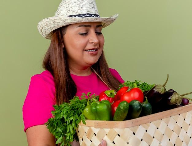 エプロンと帽子をかぶった中年の庭師の女性は、明るい背景の上に立って幸せそうな顔で笑顔の野菜でいっぱいの木枠を保持しています